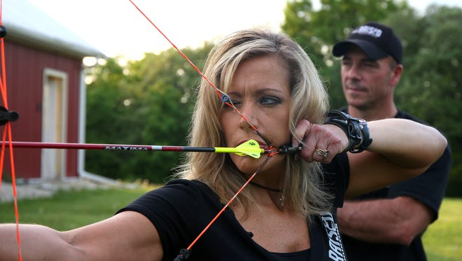 """Karin Holder takes aim with her arrow as her husband, David, stands behind during archery practice on Tuesday, May 27, 2014, at their home in rural Winterset. The couple, along with their two children, Warren and Easton, are producing a television show that will premier on the Outdoor Channel on July 5, called """"Raised Hunting."""""""