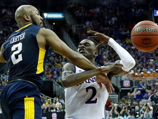 West Virginia's Jevon Carter knocks the ball away from Kansas' Lagerald Vick during the second half of the NCAA college basketball championship game in the Big 12 men's tournament Saturday, March 10, 2018, in Kansas City, Mo. Kansas won 81-70. (AP Photo/Charlie Riedel)