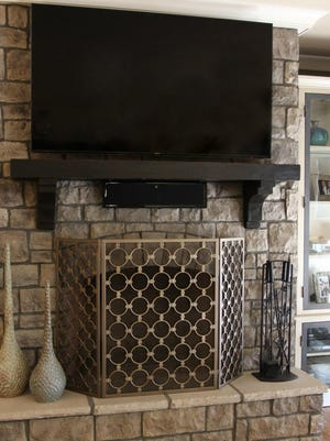 AFTER: The black chalk paint makes the gray stone fireplace stand out beautifully.