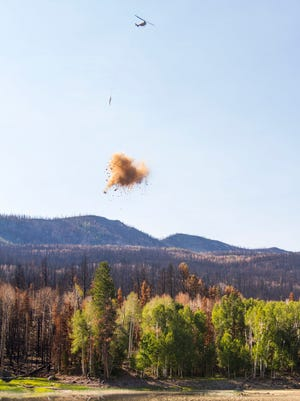 A helicopter drops mulch over the Yankee Meadows area to help seeds grow and rehabilitate wildlife after the Brian Head fire, Wednesday, August 30, 2017.