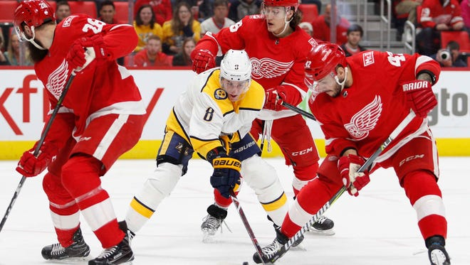 Feb 20, 2018; Detroit, MI, USA; Nashville Predators center Kyle Turris (8) tries to control the puck against Detroit Red Wings right wing Luke Witkowski (28) left wing Tyler Bertuzzi (59) and right wing Martin Frk (42) during the first period at Little Caesars Arena. Mandatory Credit: Raj Mehta-USA TODAY Sports