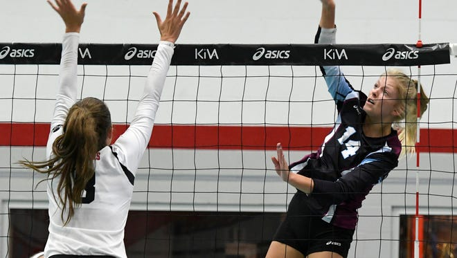 Assumption's Anna DeBeer, right, attempts to score past the defense of Walton's Caroline Cheney during the championship match of the Louisville Invitational Volleyball Tournament at the Ohio Valley Volleyball Center, Saturday, Sep. 9, 2017 in Louisville.