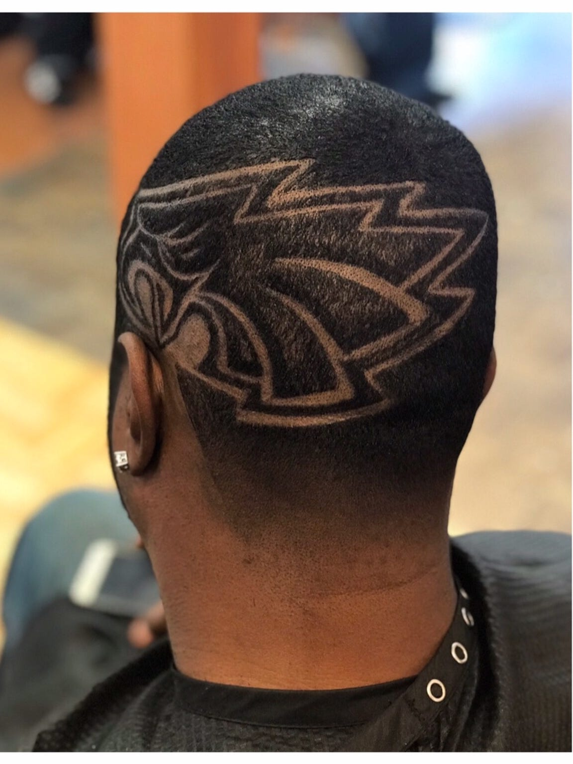 Curt Dudley shows off his Eagles-related hair design crafted by Jonathan Oliphant, owner and operator of The Hair Factory in Burlington City.