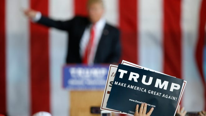A supporter holds a sign as Republican presidential candidate Donald Trump speaks at a rally, Friday, May 6, 2016, in Omaha, Neb. (AP Photo/Charlie Neibergall)