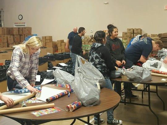 Ruidoso High School volunteers wrap presents.