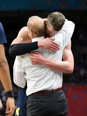 Michigan head coach John Beilein hugs Michigan forward Moritz Wagner as he exits the game.