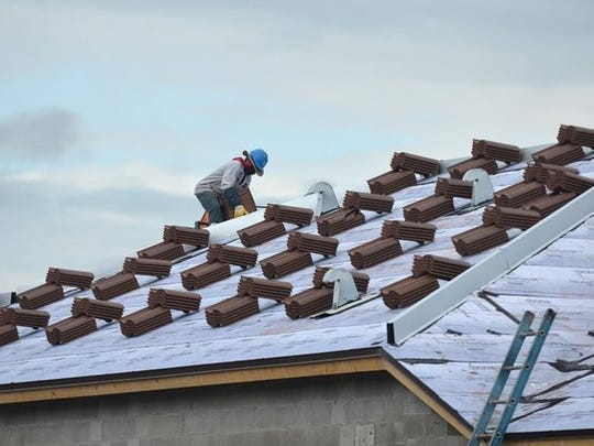 Mackenson Vilius of Latite Roofing loads tile onto a roof on Ferrari Ave in Ave Maria in 2016.