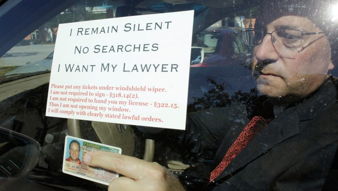 Attorney Warren Redlich holds up a flier he designed. The DUI attorney contends that when a driver approaches a police drunken-driving checkpoint, they don't have to speak to the officers.