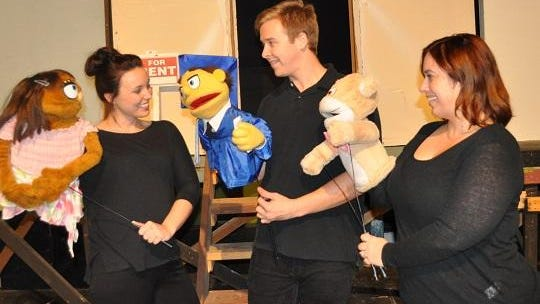 Katie (Lesley Harrison) is greeted by Princeton (Tyler Jarrett) and The Bad Idea Bear (Alli Smith).
