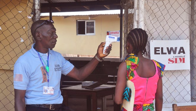 A woman has her temperature measured by a health worker before entering the Ebola clinic where a 10-year-old boy is being treated for Ebola on the outskirts of Monrovia, Liberia, Friday.