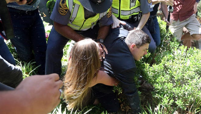 Phoebe LaFroy Stephens tackles Jason Kessler after his press conference was disrupted by protestors Sunday, Aug. 13, 2017, outside City Hall in Charlottesville, Va. The previous day, a woman was killed and several others injured after the Unite the Right rally, organized by Kessler.