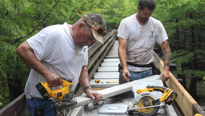 Willie Brown, right, and James Simpson, work to cut notches in planks for the boardwalk at Six Mile Cypress Slough Preserve during a renovation project on Monday.