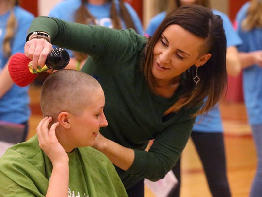 "Riverdale junior Ariana Cauthon touches her shaved head for the first time as hairdresser Terra Henderson, from Tease Salon, brushes away loose hair after shaving Cauthon's head during Riverdale's 4th annual St. Baldrick's Event ""Brave the Shave"" Event on Friday, March 17, 2017. Riverdale raised over $20,000 to fight childhood cancer during last year's event."