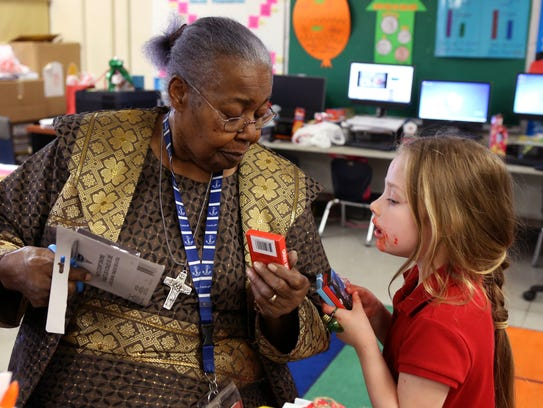 Gladys Tilley (left), 82, hands out games to Hannah Neil, 5, to be distributed during her kindergarten classroom Christmas party at Meadowbrook Elementary. Tilley has taught kindergarten for 40 years and has been an educator for 50. She also taught first grade for a very short time.