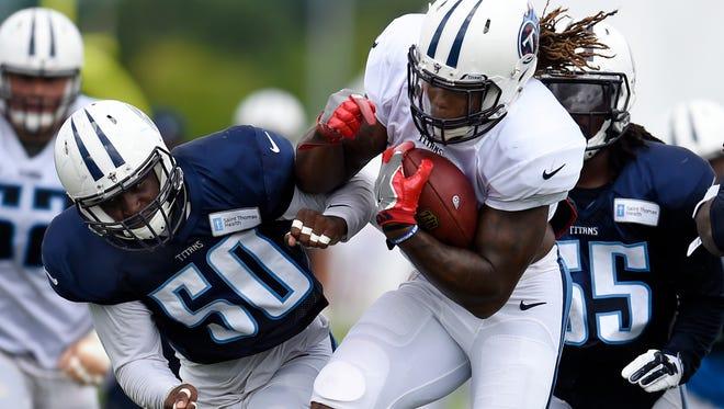 Titans running back Derrick Henry (2) powers through linebacker Nate Palmer (50) during practice Thursday at Saint Thomas Sports Park.