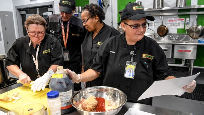 Karen Klopfenstein, right, a cook Summit Drive Elementary School, looks over a recipe using certified Angus beef in the meat loaf during a Greenville County school food summer workshop at the Enoree Career Center in Greenville on Tuesday. Greenville County is the first district in the nation to be licensed to serve certified Angus beef, director Joe Urban said. Preparing food near Klopfenstein, from left; Jackie Nelson, Brian Hickey, and Carolyn Byrd.