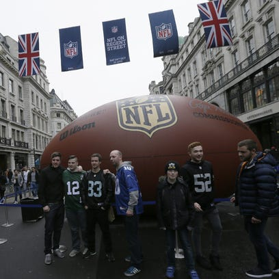 Football fans pose for pictures during an NFL fan rally