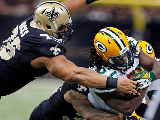 Green Bay Packers running back Eddie Lacy (27) is tackled by New Orleans Saints defensive end Akiem Hicks (76) and strong safety Kenny Vaccaro in the second half of an NFL football game in New Orleans, Sunday, Oct. 26, 2014. (AP Photo/Rogelio Solis)