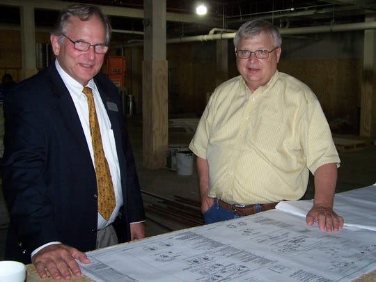 Bill Boykin, right, and Cary Karlson, left, of the Washington County Economic Alliance review the plans of The Lofts at 517 located in the historic Sears Roebuck and Co. building.