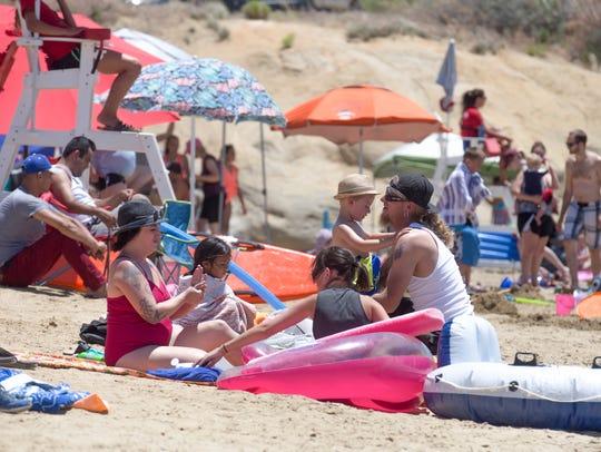 Beach-goers enjoy the sun Monday at Farmington Lake.