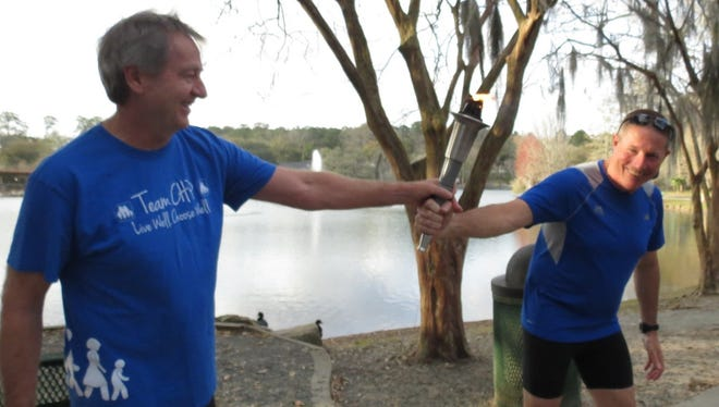 Dr. Dehler, representing Capital Health Plan, a sponsor of the Capital City Senior Games, hands off the torch to County Commissioner Bryan Desloge, during the Annual Torch Run for a previous Senior Games.