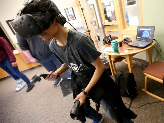 Sebastian Flores, 16, tries out a virtual reality game in the library of Kingston High School on Friday.