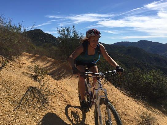 Corrine Banks rides her bike along the San Juan Mountain