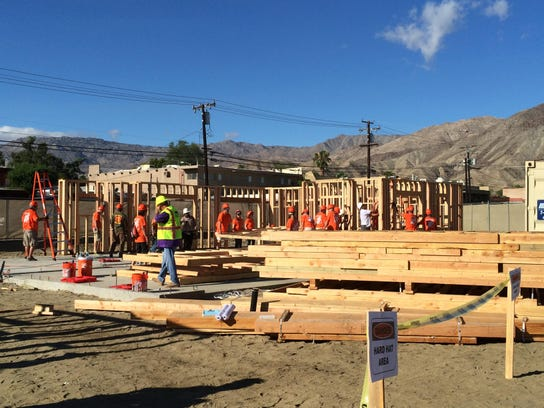 Volunteers raise the frames on two Habitat for Humanity