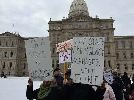 Flint water protesters hold signs condemning Governor