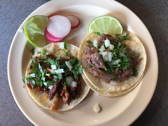 A tender cabeza taco and a juicy, slightly crisp pastor taco from Tacos El Rey 3 is South Reno. The tacos await spurts of lime juice.