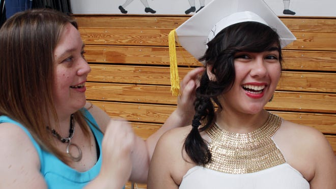 Stissing Mountain High graduate Cristina Cummings gets some assistance with her cap from math teacher Jen Griffin.