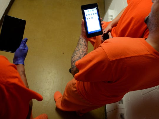A group of inmates hold their tablets in their hands Monday, Dec. 28, at the Sanilac County jail in Sandusky.