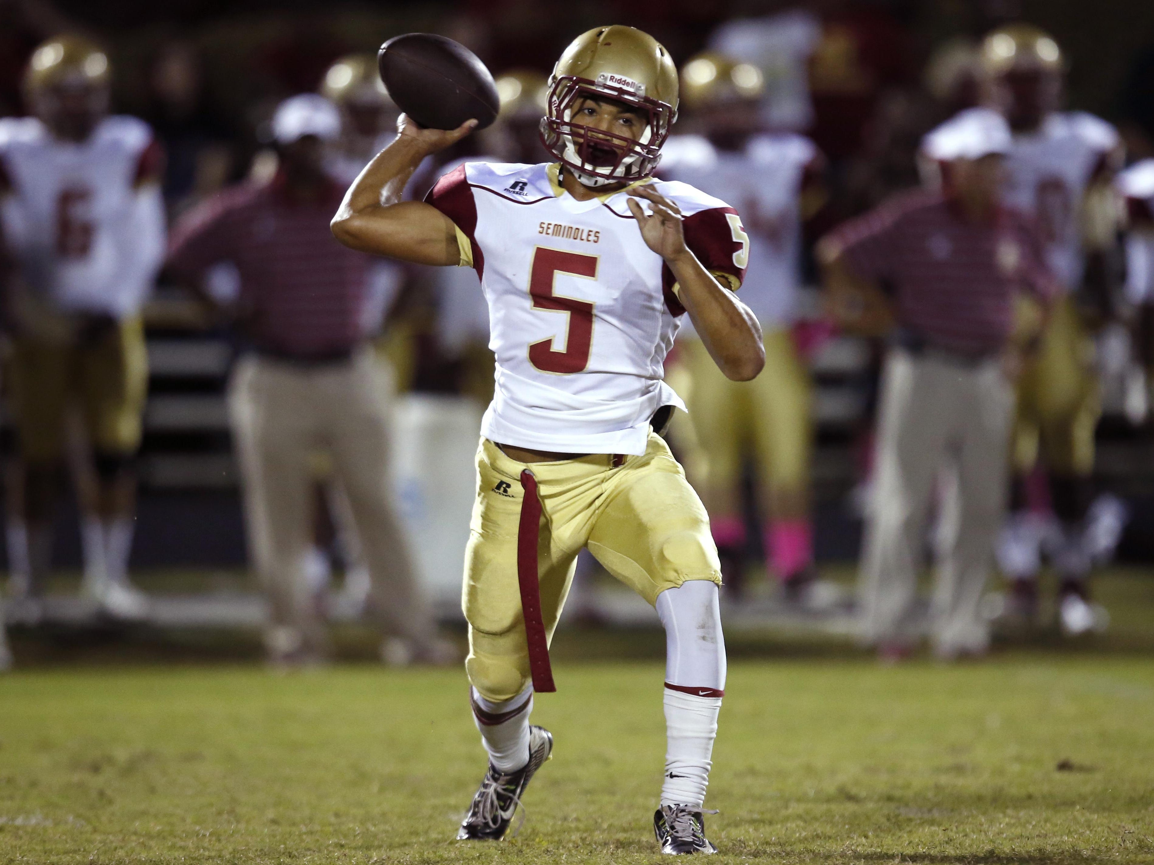 Florida High's Isaiah Hill throws a pass against NFC during their game on Friday. Hill threw 4 touchdowns on the night and ran for another score in overtime.