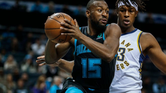 Charlotte Hornets guard Kemba Walker, left, looks to pass the ball as Indiana Pacers center Myles Turner defends during the first half of an NBA basketball game in Charlotte, N.C., Wednesday, Nov. 21, 2018. (AP Photo/Nell Redmond)