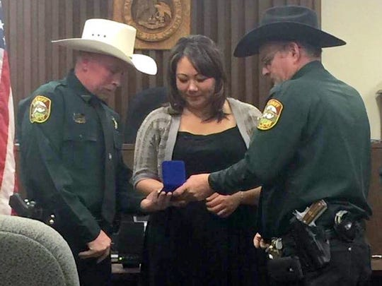 Lincoln County Sheriff Robert Shepperd, right, shows Deputy Jason Green and his wife the Purple Heart award.