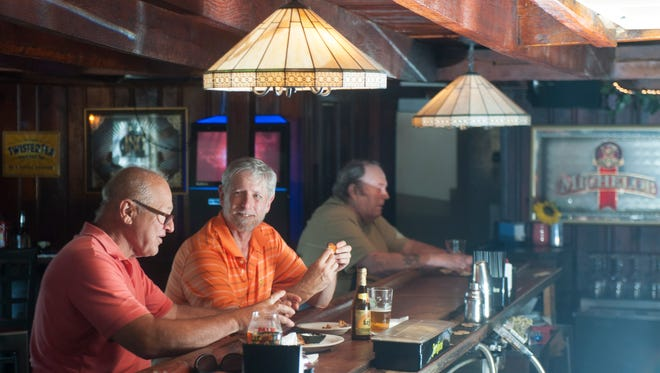Longtime friends Chuck Leone of Mickleton (left) and Don Emery of West Chester, Pennsylvania, (center) dine on chicken wings at the Barnsboro Inn in Sewell.