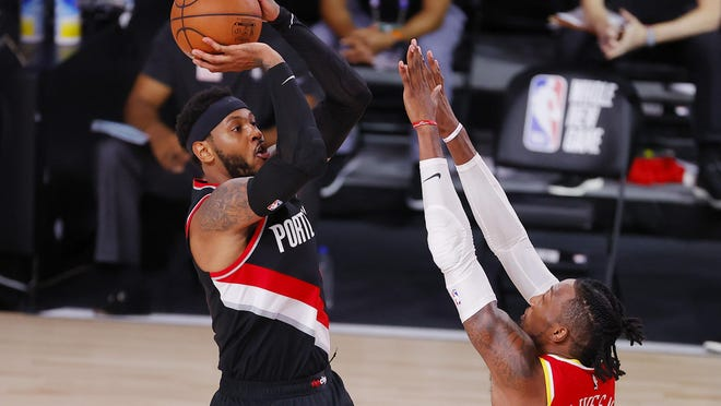 Portland's Carmelo Anthony (left) shoots against Houston's Robert Covington during the second half on Tuesday.