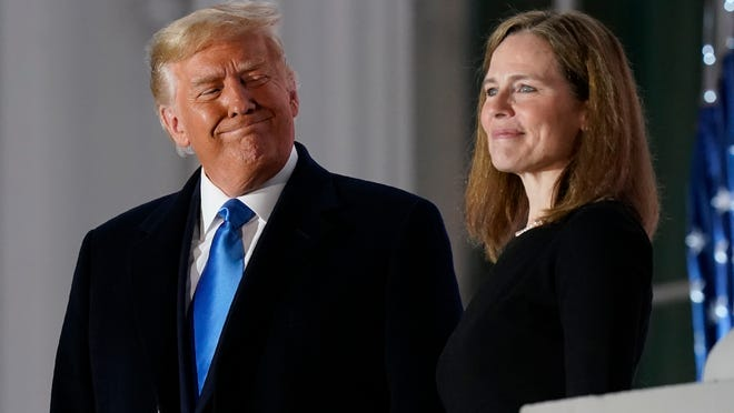 President Donald Trump and Amy Coney Barrett stand on the Blue Room Balcony after Supreme Court Justice Clarence Thomas administered the Constitutional Oath to her on the South Lawn of the White House White House in Washington, Monday, Oct. 26, 2020. Barrett was confirmed to be a Supreme Court justice by the Senate earlier in the evening.