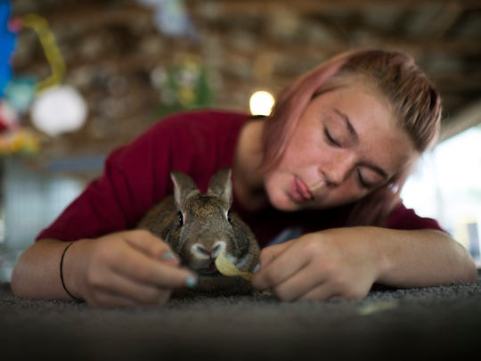 Madison Hoban, 15, treats her rabbit Nugget to a potato
