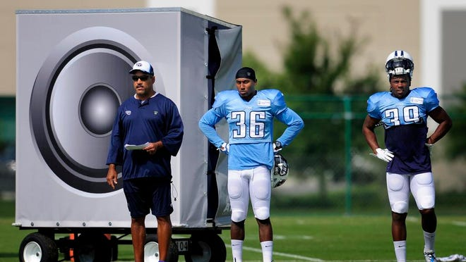Titans assistant defensive backs coach Steve Brown stands in front of one of the giant speakers that were placed on the practice field to simulate crowd noise.