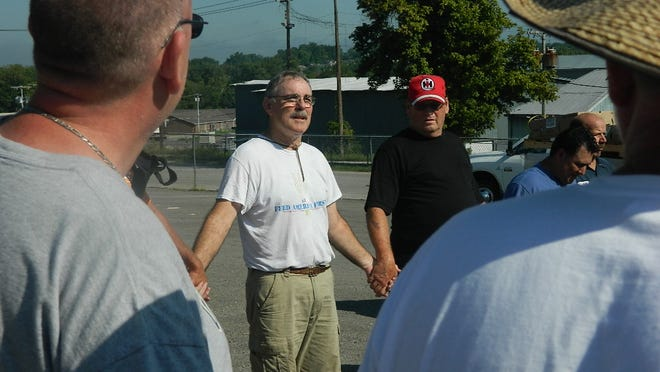 Tom Henry leads a prayer before the food is distributed among agencies in Clarksville.