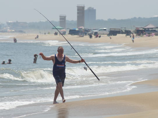 A fisherman carries his line back to shore at a drive-on