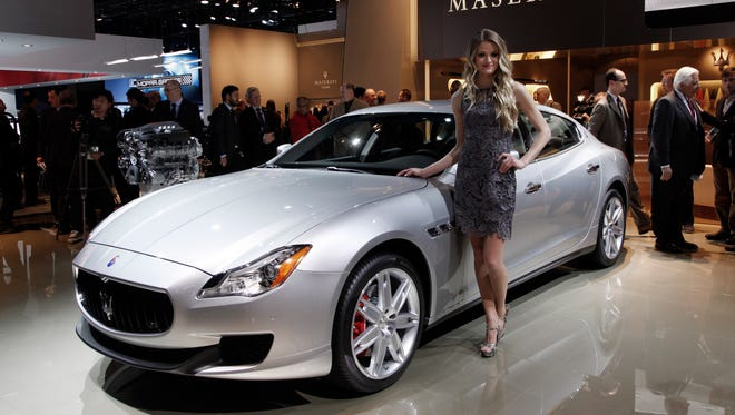 A model poses with the Maserati Quattroporte at media previews for the North American International Auto Show in Detroit in 2013.