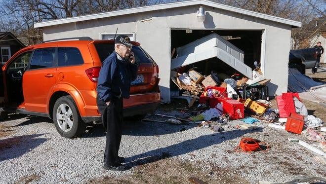 Russell Fisher talks with his insurance company as police investigate the scene of an accident on North Hampton Avenue just south of Commercial Street on Tuesday, Feb. 7, 2017. A suspect was fleeing from police when he crashed through a utility pole into Fisher's garage, causing damage to the structure and a white minivan.