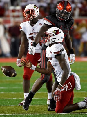 Houston linebacker Steven Taylor, top, stares at Louisville quarterback Lamar Jackson after tackling Jackson for a loss during the second half.