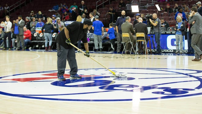 A maintenance crew member attempts to mop excessive moister off the court surface of the Wells Fargo Center before a game between the Philadelphia 76ers and the Sacramento Kings.