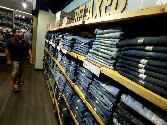 A shopper at a J.C. Penney store in New York visits the Arizona brand jeans display for young men. Sales of jeans in the U.S. fell 6 percent during the year that ended in June.