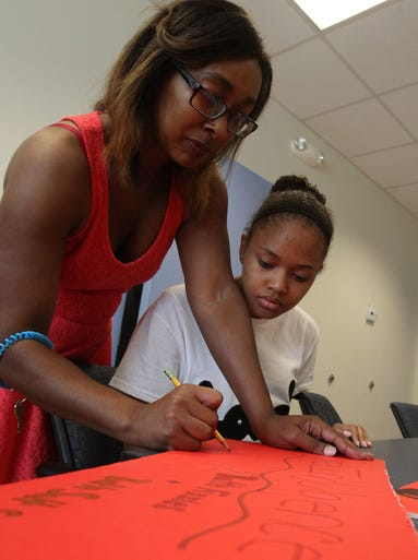 Kids In Biz CEO  Melissa Williams works with Alyzee Corder on her poster for the Kids In Biz Expo this Saturday.