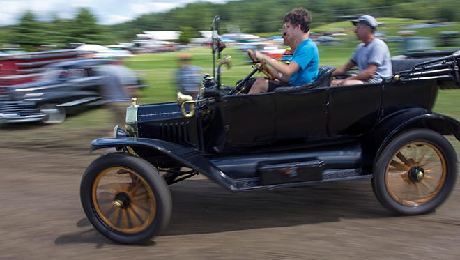 Jeremy Laganiere, 15, drives his grandfather's antique car as his parents Jean and Helen Laganiere ride along around the show grounds during the 57th annual Stowe Antique & Classic Car Meet in Stowe on Friday, August 8, 2014.