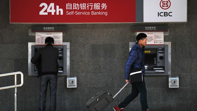 Chinese consumers uses an ATM machine at the entrance of a bank in Beijing